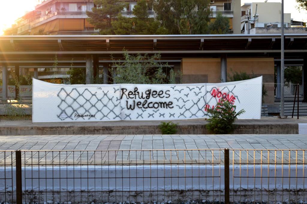 """Kontraste in Athen kurz vor den Neuwahlen: Eine Gruß an weiterreisende Flüchtlinge auf dem Athener Hauptbahnhof. Einige Meter entfernt demonstriert die rechtsradikale Partei """"Goldene Morgenröte""""."""